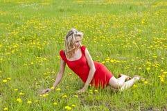 Jeune femme s'asseyant dans le pré Photo stock