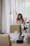 Jeune femme s'asseyant dans un café utilisant son téléphone Image stock