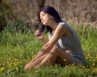 Jeune femme s'asseyant dans un domaine photographie stock libre de droits