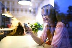 Jeune femme s'asseyant dans un restaurant utilisant un mobile photos stock