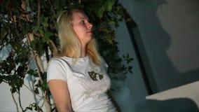 Jeune femme s'asseyant dehors dans la station de vacances la nuit banque de vidéos
