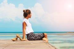 Jeune femme s'asseyant devant la lumière du soleil Indépendant de Madame travaillant à la plage photo stock
