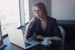 Jeune femme s'asseyant en café Image stock
