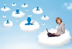 Jeune femme s'asseyant en nuage avec l'ordinateur portable Photographie stock