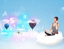 Jeune femme s'asseyant en nuage avec l'ordinateur portable Images stock
