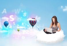 Jeune femme s'asseyant en nuage avec l'ordinateur portable Photo stock