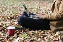 Jeune femme s'asseyant en parc avec l'ordinateur portable et le café Photographie stock