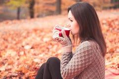 Jeune femme s'asseyant en parc et thé potable Photos libres de droits