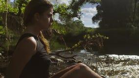 Jeune femme s'asseyant en rivière en eau peu profonde clips vidéos