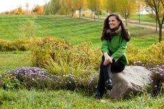 Jeune femme s'asseyant en stationnement d'automne Image libre de droits