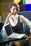 Jeune femme s'asseyant à la table avec l'ordinateur portable Images libres de droits