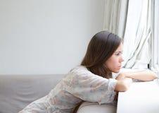 Jeune femme s'asseyant seul regardant la fenêtre image libre de droits