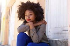 Jeune femme s'asseyant sur des étapes en dehors de la porte semblant sérieuse Photo libre de droits