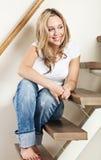 Jeune femme s'asseyant sur des opérations Photo stock
