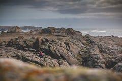 Jeune femme s'asseyant sur des roches de l'île de Yeu photographie stock