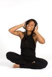 Jeune femme s'asseyant sur l'étage écoutant la musique Photo stock