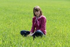 Jeune femme s'asseyant sur l'herbe Photographie stock