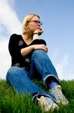 Jeune femme s'asseyant sur l'herbe photos stock