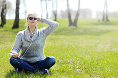 Jeune femme s'asseyant sur l'herbe en parc sélectionnant la musique sur le smartpho Photo stock