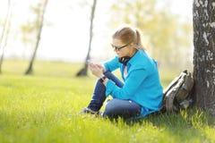 Jeune femme s'asseyant sur l'herbe en parc sélectionnant la musique sur le smartpho Photos libres de droits