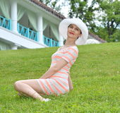 Jeune femme s'asseyant sur l'herbe verte Images libres de droits