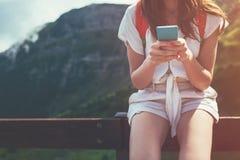 Jeune femme s'asseyant sur la barrière avec le smartphone Chemin touristique de hautes montagnes Communication numérique Textoter photo stock