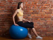 Jeune femme s'asseyant sur la boule, sur le fond de mur de briques Images stock