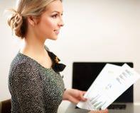 Jeune femme s'asseyant sur la chaise et tenant des papiers, Photographie stock