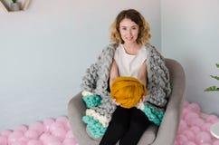 Jeune femme s'asseyant sur la chaise et tenant la laine mérinos dans des mains Image libre de droits