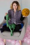 Jeune femme s'asseyant sur la chaise et tenant la laine mérinos dans des mains Photographie stock libre de droits