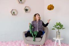 Jeune femme s'asseyant sur la chaise et tenant la laine mérinos dans des mains Image stock