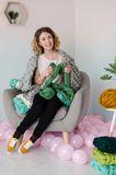 Jeune femme s'asseyant sur la chaise et tenant la laine mérinos dans des mains Photos stock