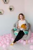 Jeune femme s'asseyant sur la chaise et tenant la laine mérinos dans des mains Photographie stock