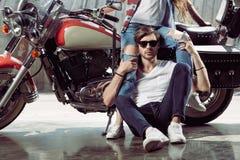 Jeune femme s'asseyant sur la moto et l'homme élégant dans des lunettes de soleil regardant l'appareil-photo Photos stock