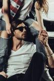 Jeune femme s'asseyant sur la moto et l'homme élégant dans des lunettes de soleil regardant loin Photographie stock