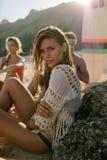 Jeune femme s'asseyant sur la plage avec ses amis Photo libre de droits