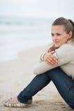 Jeune femme s'asseyant sur la plage isolée examinant la distance Images stock