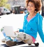 Jeune femme s'asseyant sur la planche à roulettes avec l'ordinateur portable Photo stock