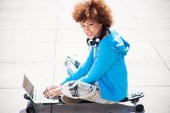 Jeune femme s'asseyant sur la planche à roulettes avec l'ordinateur portable Image stock