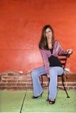 Jeune femme s'asseyant sur la présidence Photographie stock libre de droits