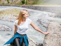 Jeune femme s'asseyant sur la roche en rivière rapide de montagne et éclaboussant sur le fond extérieur de l'espace de copie d'ét photos stock
