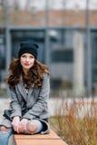Jeune femme s'asseyant sur la rue photo stock