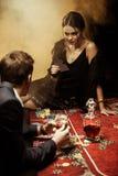 Jeune femme s'asseyant sur la table de tisonnier et jouant le tisonnier avec l'homme dans le costume image libre de droits