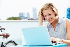 Jeune femme s'asseyant sur la terrasse de toit utilisant l'ordinateur portable Photographie stock libre de droits