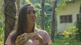 Jeune femme s'asseyant sur le banc au village asiatique de campagne et mangeant le casse-croûte banque de vidéos
