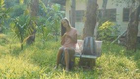 Jeune femme s'asseyant sur le banc au village asiatique de campagne et mangeant la banane banque de vidéos