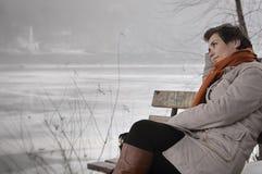 Jeune femme s'asseyant sur le banc de parc photos stock