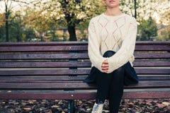 Jeune femme s'asseyant sur le banc de stationnement Photo stock