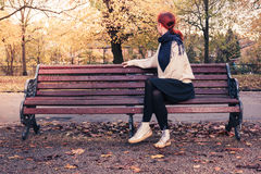 Jeune femme s'asseyant sur le banc de stationnement Photos stock