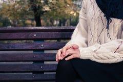 Jeune femme s'asseyant sur le banc de stationnement Image libre de droits